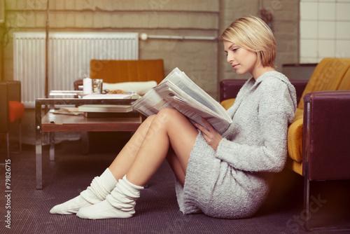 Leinwanddruck Bild entspannte junge frau liest die tageszeitung