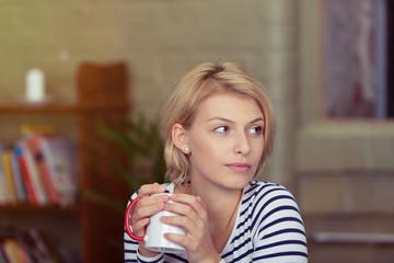 junge blonde frau mit einer tasse tee schaut zur seite