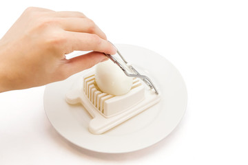 cutting an egg with an egg slicer