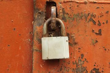 Old padlock on the metal door abstract background