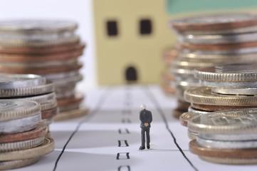 お金の山とゴールを見つめる男性