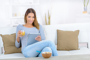 Woman using her tablet computer during breakfast
