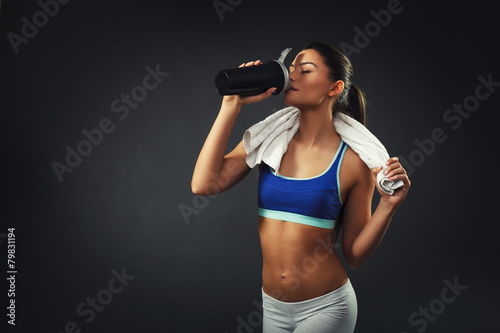 Attractive young woman drinking proteins - 79831194