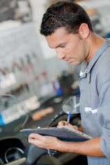 Mechanic writing on his clipboard
