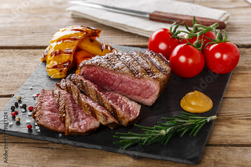 Fotografiet grilled beef steak rare sliced with vegetables