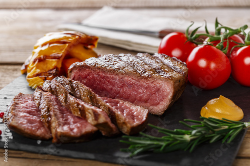 Poster grilled beef steak rare sliced with vegetables