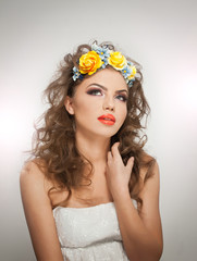 Portrait of beautiful girl in studio with yellow roses in hair