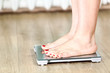 Close up of Caucasian female legs standing on the floor scales