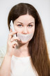 Woman with sad eyes with mouth sealed and mobile phone