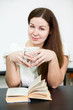 Young woman reading book while sitting at table with tea cup