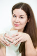Facial portrait of young woman with tea mug in hand