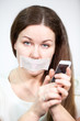 Sad woman with mouth sealed tape holding mobile phone in hands