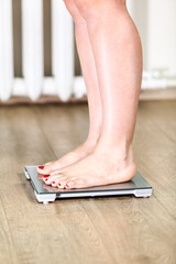Caucasian woman with bare feet is on floor weight scales