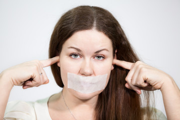 Caucasian young woman with mouth sealed and plugged ears