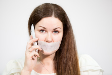 Attractive woman with tape on mouth tryes to call mobile phone