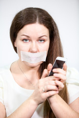 Caucasian woman with mouth sealed tape holds cell phone in hands