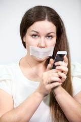 Attractive woman with mouth sealed can not talk on a cell phone