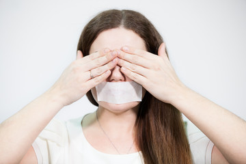 Caucasian woman covering her eyes with hands, mouth sealed tape