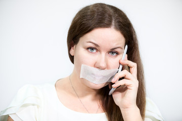 Woman with cellphone, tape on mouth, grey background
