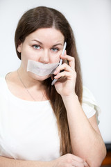 Sad woman with cellphone and tape on her mouth, grey background