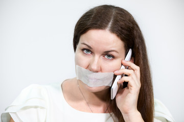 Sad brunette woman with cellphone and tape on her lips