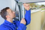 Man installing a garage door - 79836948