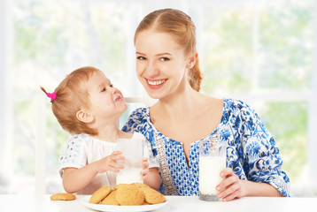 happy family mother and baby daughter girl at breakfast: biscuit