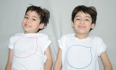 Little asian sibling boy laying down