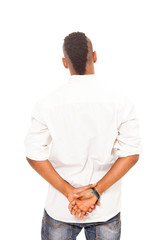 African man looking at the white wall with crossed hands behind