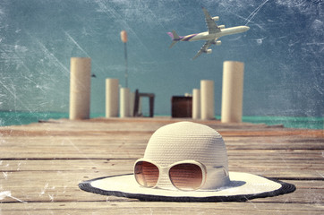 Scrated film effects. Hat and sunglasses on the wooden jetty. Ex