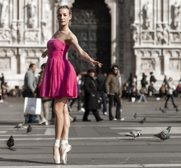 Girl dancing near Milan Cathedral Square and looking