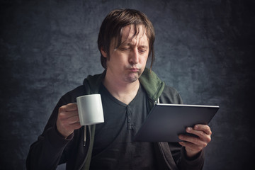 Man Reading Bad News on Digital Tablet Computer