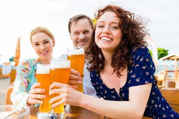 Freunde prosten mit Bier im Biergraten