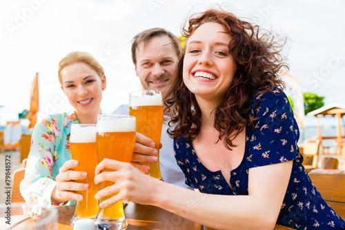 Freunde prosten mit Bier im Biergraten  - 79848572