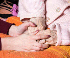 Caring hands holding old lady's hands at home
