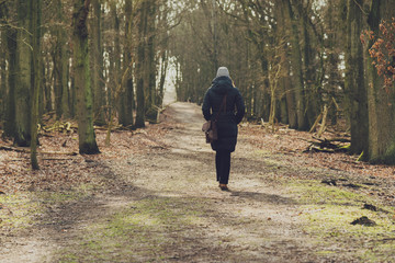 Woman walking along a woodland track