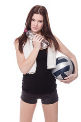 Healthy sporty girl with volleyball, bottle of water and towels