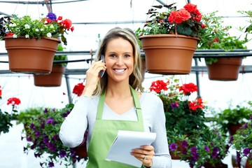 Florist woman working with flowers in greenhouse.