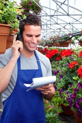 Florist man working with flowers in greenhouse.