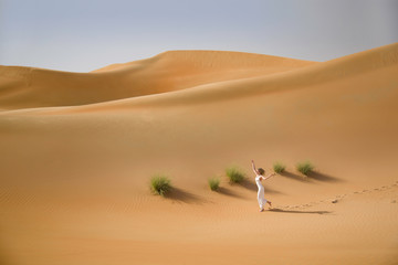 Beautiful sand dunes, a slim running woman in white dress