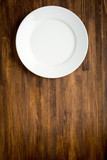 Empty white plate on wooden table - 79854729