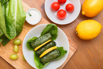 Turkish sarma with lemons, tomatoes, lettuce top view