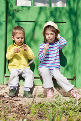 Little brother and sister sitting in front of the rustic door