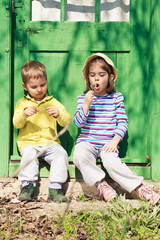 Two kids sitting in front of the rustic green door