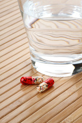 Glass of Water and Medicine Capsules
