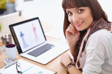 Portrait of attractive female fashion designer sitting at office
