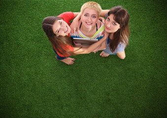 Three women with naked feet standing in grass holding laptop