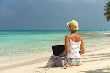Woman on exotic tropical beach with laptop computer