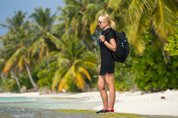 Young tourist with backpack walking in tropical beach