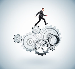 businessman runs in gears